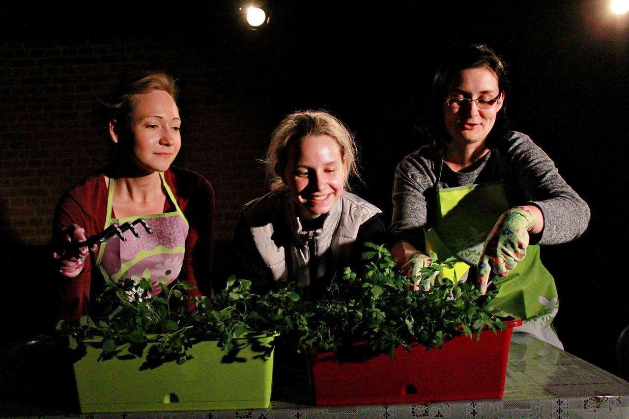 Zdjęcie z projektu Dzielnica cudów. Trzy aktorki pochylone nad doniczkami z roslinami, usmiechają się i pielą.