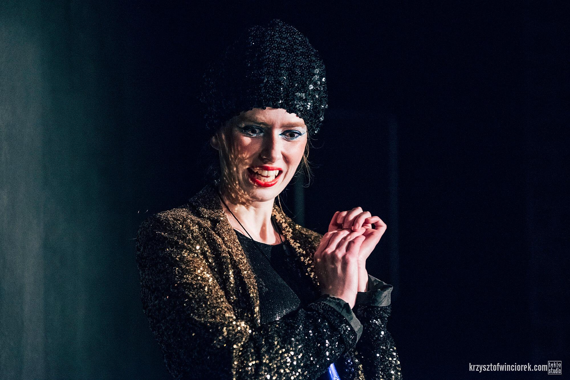 Zdjęcie z festiwalu Pociąg do miasta. Aktorka ubrana w cekinową marynarkę i czapkę. Widac jej zęby. Ręce ma splecione przed sobą.