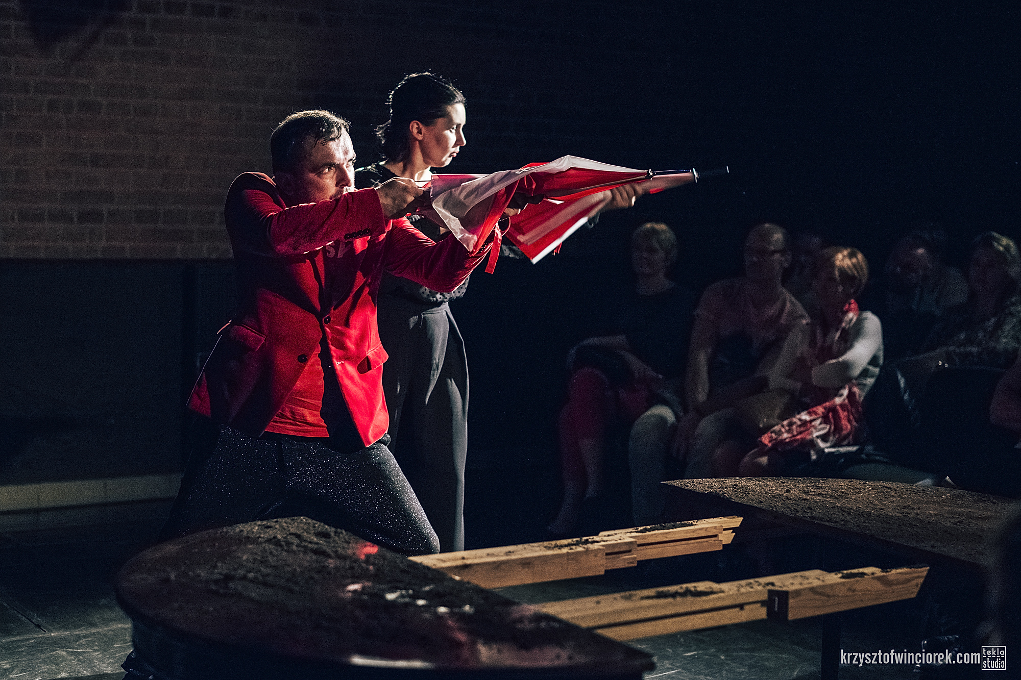 Zdjęcie z festiwalu Pociąg do miasta. Aktor i aktorka mierzą do widzów z czerwono białych parasolek imitujących karabiny.
