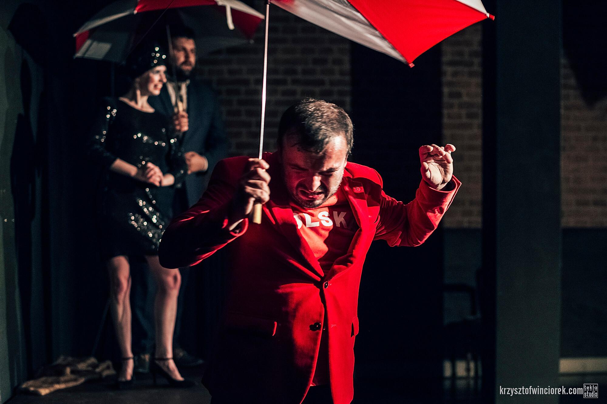 Zdjęcie z festiwalu Pociąg do miasta. Aktor w czerwonej marynarce i czerwonek koszulce z napisem Polska, pod parasolką. Imituje ucieczkę przed deszczem.