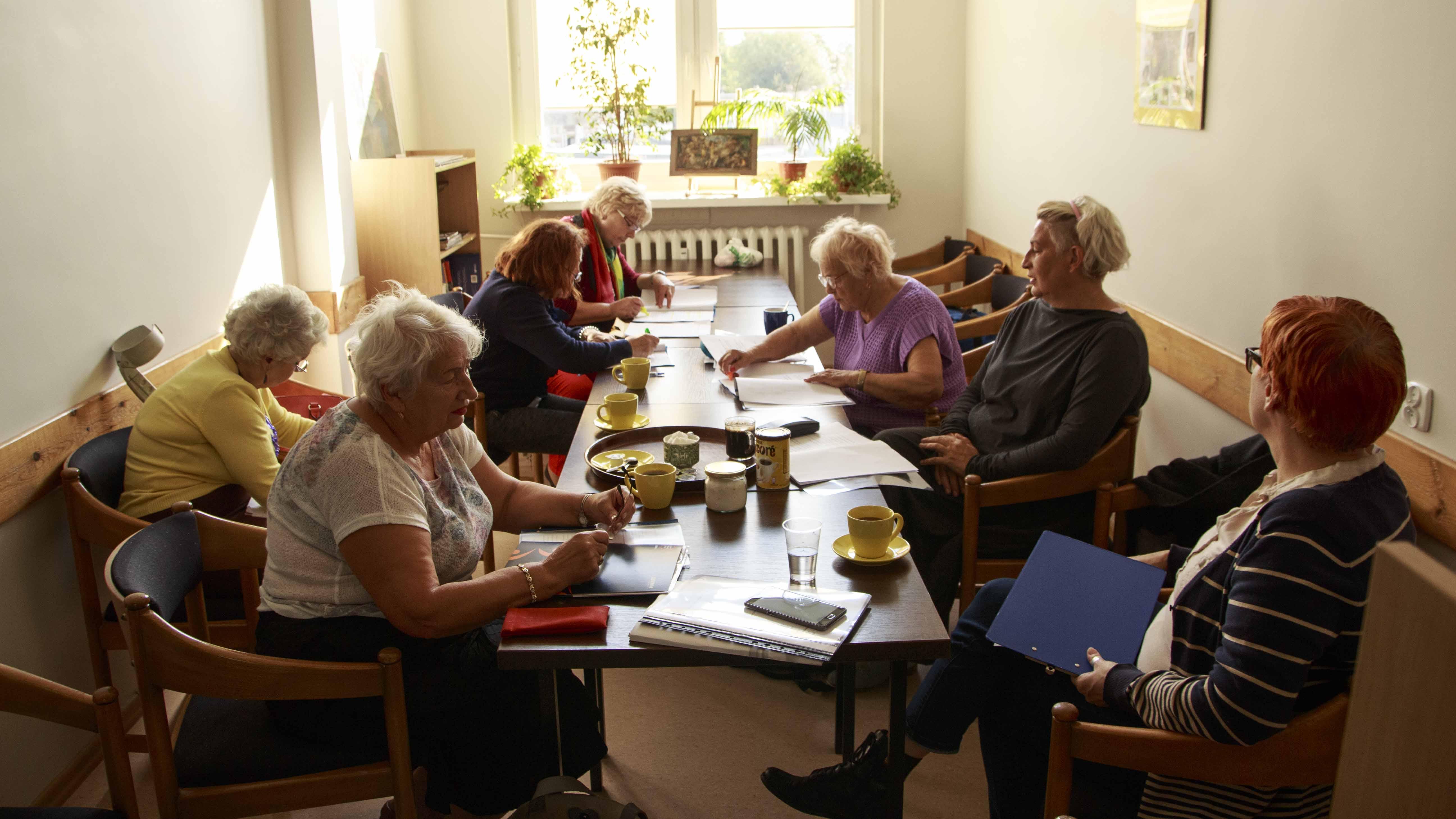 Zdjęcie z projektu Chór dzielnicowy. Kilka starszych kobiet przy stole podczas próby, pochylonych nad scenariuszami.