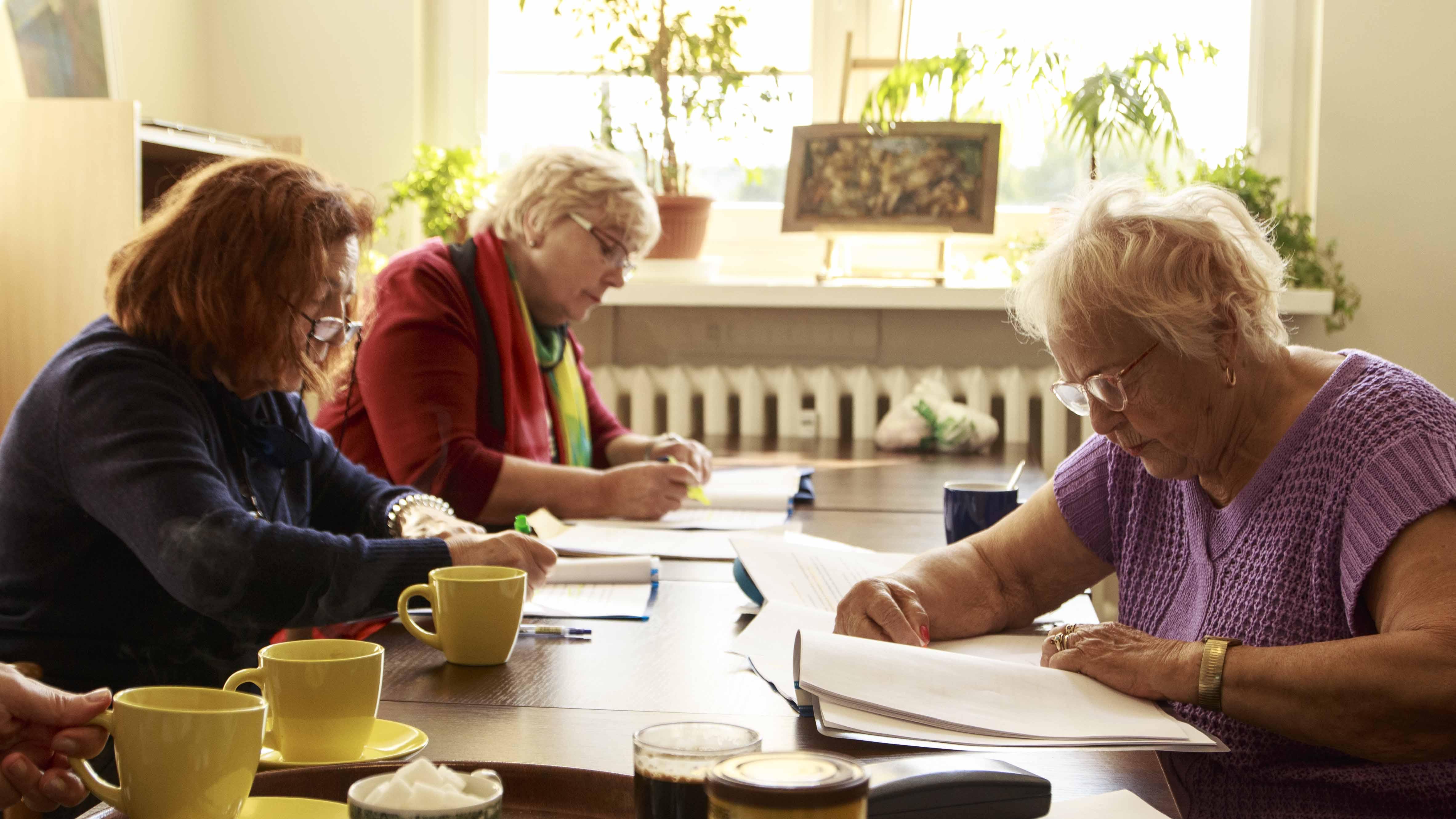 Zdjęcie z projektu Chór dzielnicowy. Trzy starsze kobiety przy stole, pochylone nad scenariuszami.