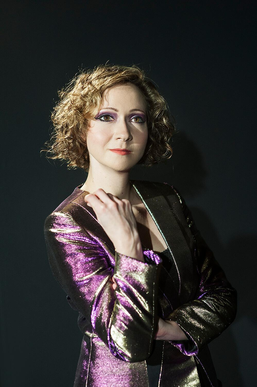 Zdjęcie do spektaklu od wesela do wesela. Portret. Aktorka w marynarce mieniącej się na fioletowo.