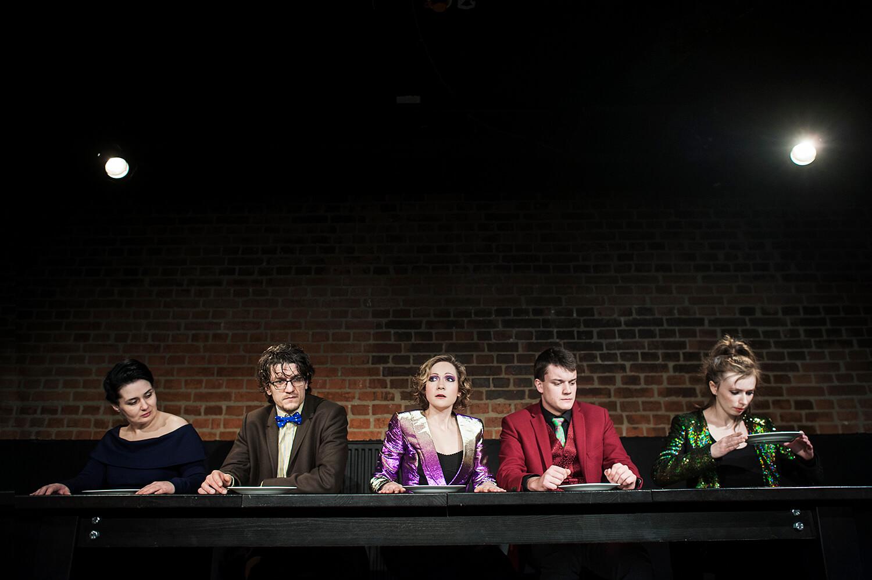 Zdjęcie do spektaklu od wesela do wesela. Piatka aktórów siedzi za stołem. Przed każdym z nich talerz.