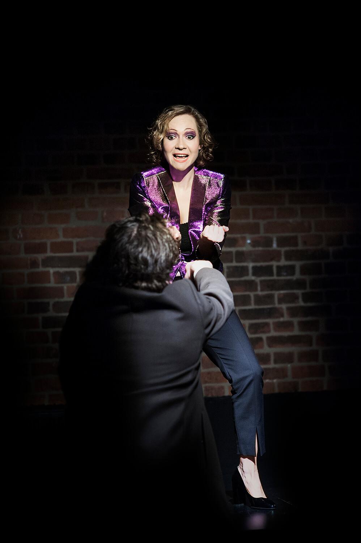 Zdjęcie do spektaklu od wesela do wesela. Aktorka stoi z zacisnietymi pięściami na stole. Przed nia aktor tyłem.
