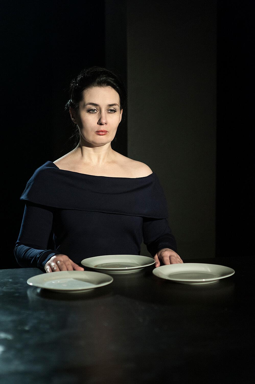 Zdjęcie do spektaklu od wesela do wesela. Aktorka w granatowej sukience siedzi za stołem, przed nia trzy białe talerze.