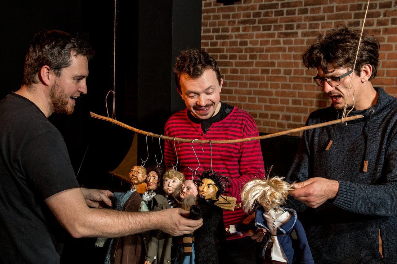 Zdjęcie do spektaklu Dzielny Kapitan Ahab. Tzrech aktorów animuje lalki zawieszone za głowy na długim kijku.