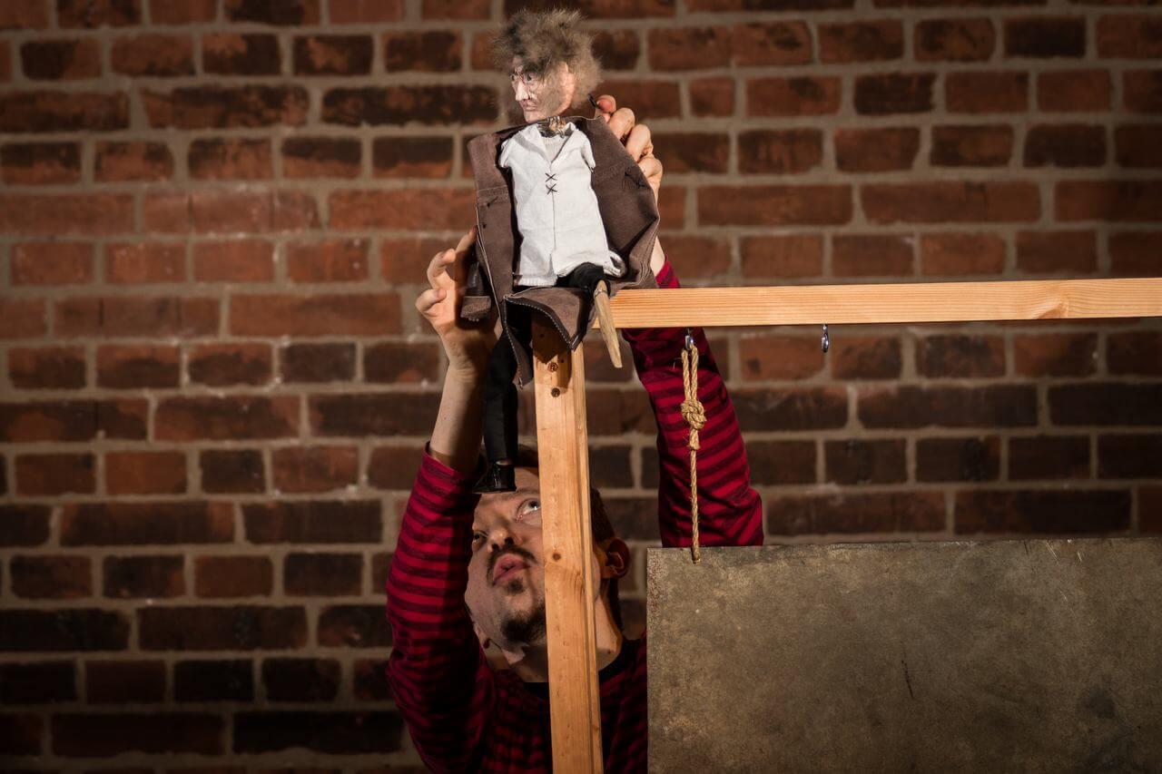 Zdjęcie do spektaklu Dzielny Kapitan Ahab. Pokazuje lalkę - Kapitana siedzącego na rogu drewnianej ramy.