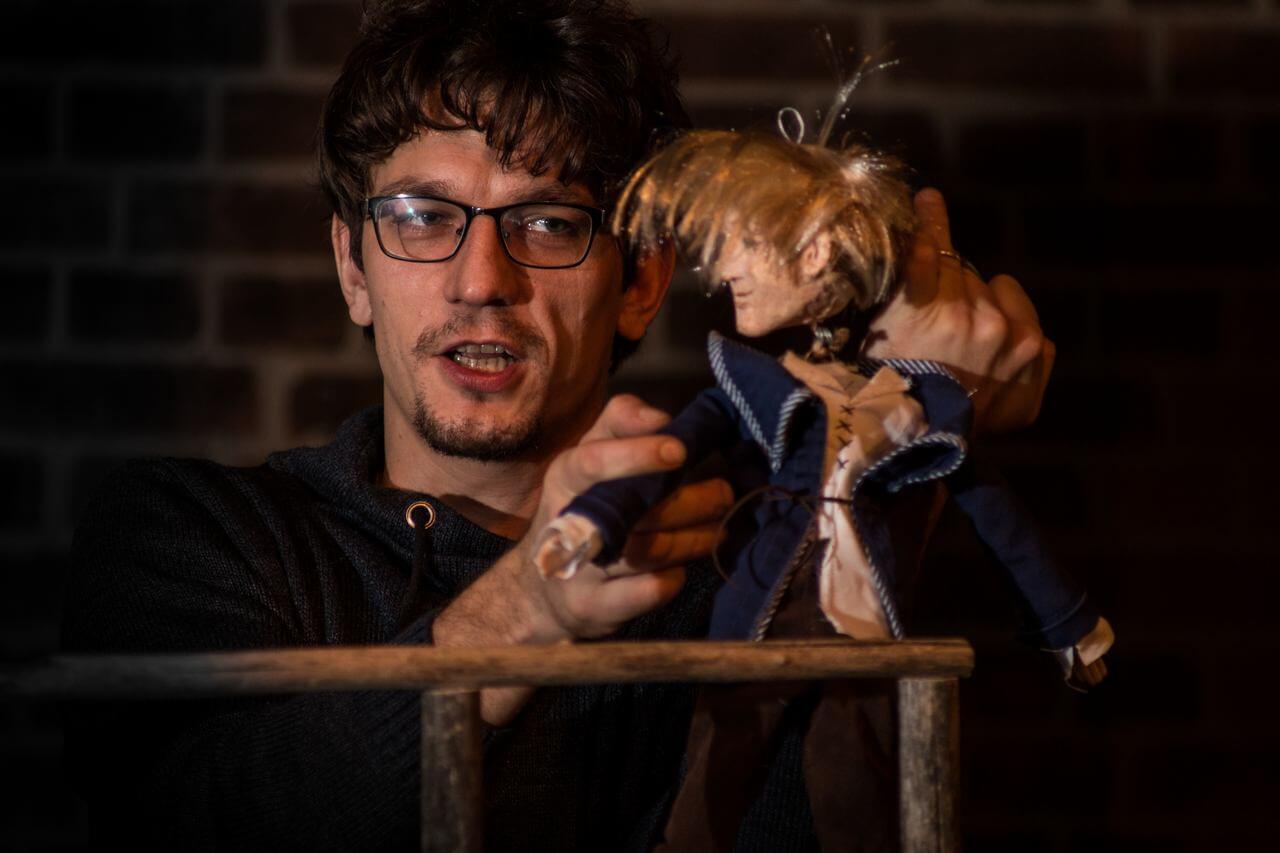 Zdjęcie do spektaklu Dzielny Kapitan Ahab. Na zdjęciu aktor w okularach animujący lalkę - chłopca w niebieskim ubraniu i blond włosach.