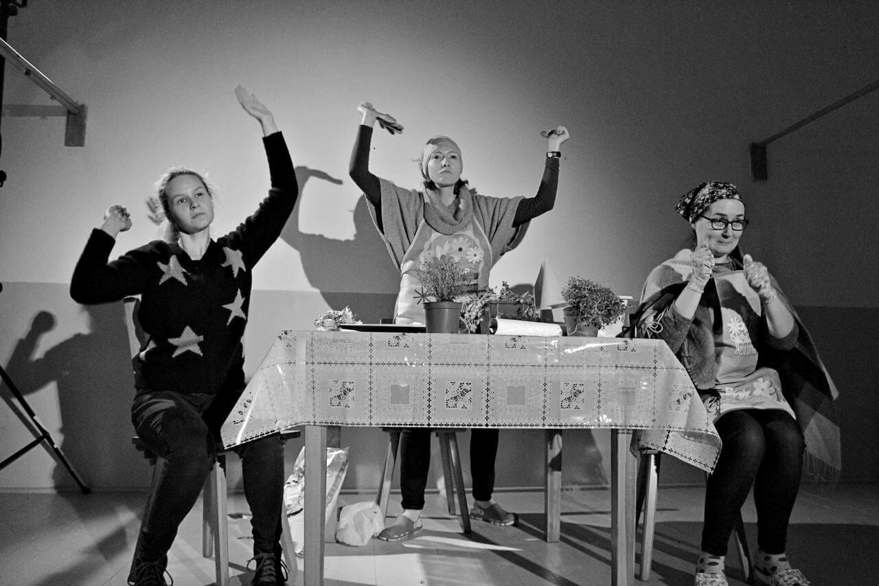 Zdjęcie z projektu Dzielnica cudów. Trzy aktorki siedza przy stole, w strojach ogrodnichych na stole doniczki z roslinami, kobiety mają uniesione ręce.