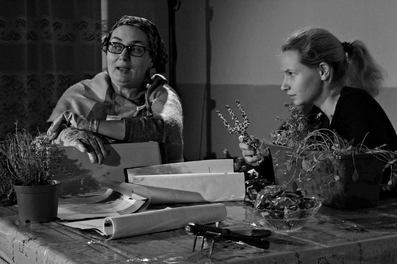 Zdjęcie z projektu Dzielnica cudów. Dwie aktorki siedzą przy stole, w strojach ogrodnichych na stole doniczki z roslinami, kobiety rozmawiają i pielą.