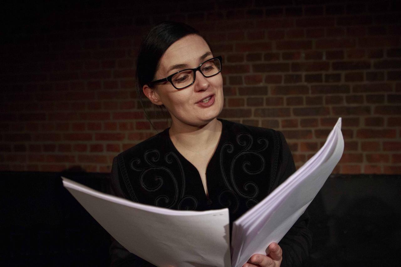 Aktorka w okularach czyta scenariusz.