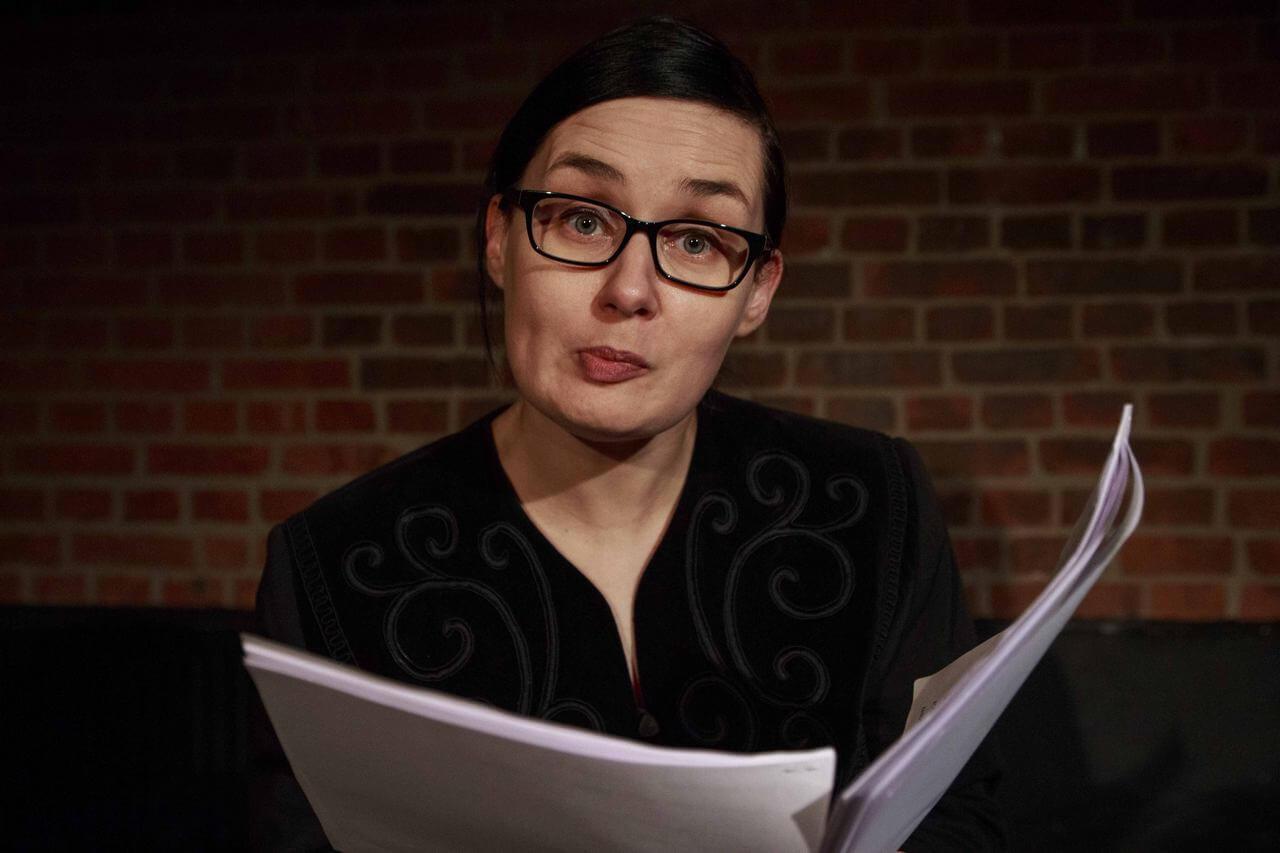 Aktorka w okularach z zaciśnietymi ustami nad scenariuszem.