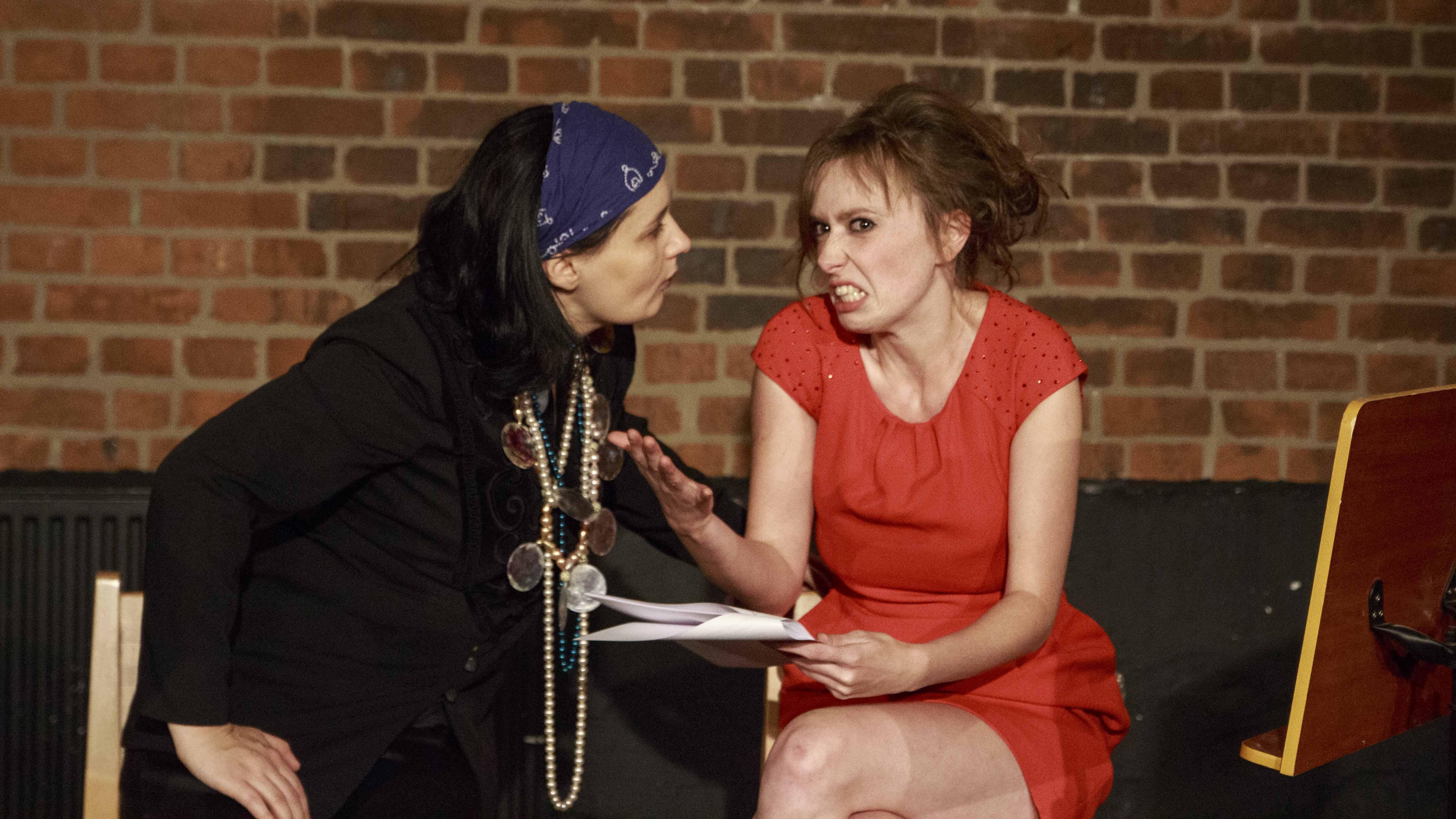 Zdjęcie ze spektaklu Dzielnice cudów. Dwie aktorki jedna aktorka w czerwonej sukience, druga aktorka przebrana jak cyganka. Rozmawiają. Aktorka w czerwonym pokazuje zęby.