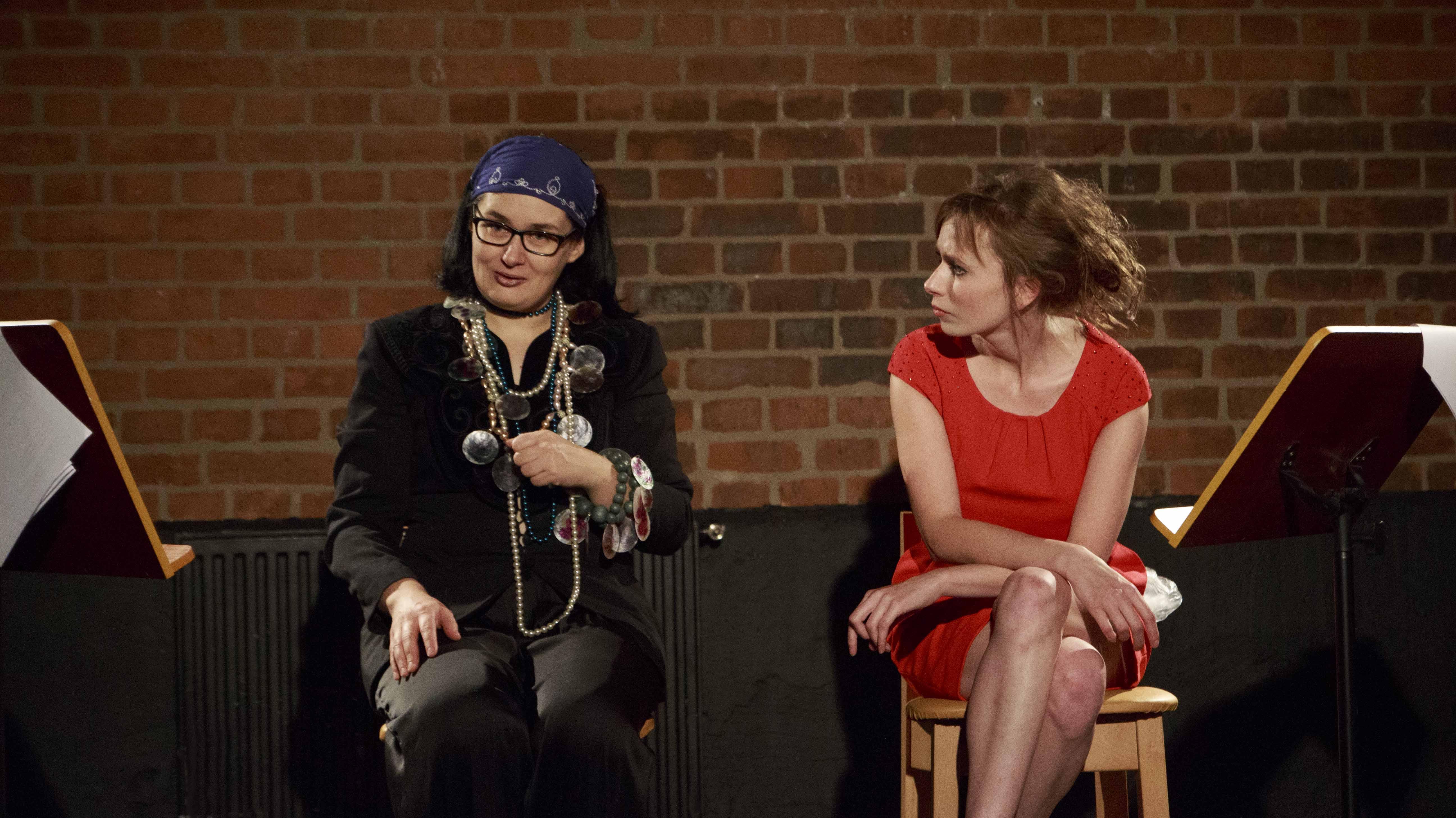 Zdjęcie ze spektaklu Dzielnice cudów. Dwie aktorki jedna aktorka w czerwonej sukience, druga aktorka przebrana jak cyganka. Rozmawiają.