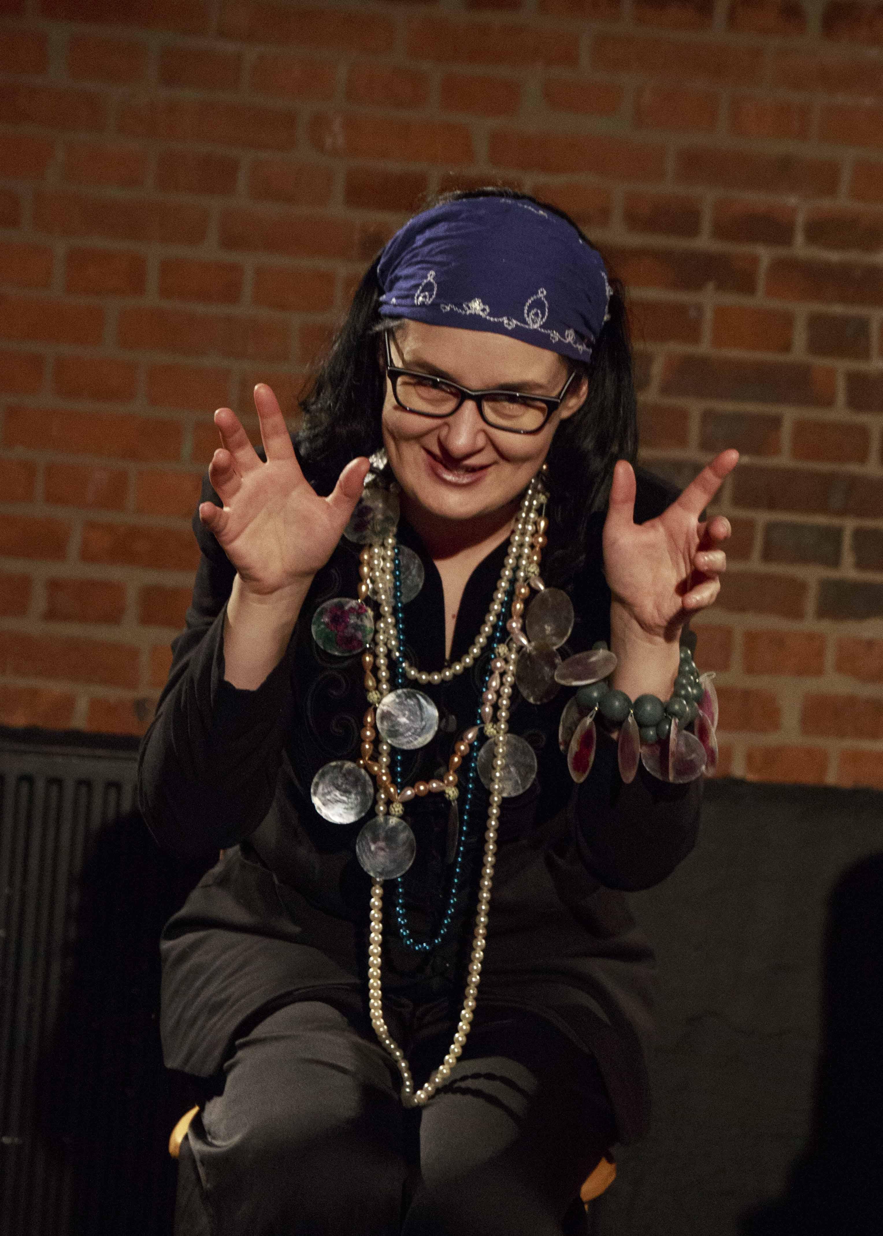 Zdjęcie ze spektaklu Dzielnice cudów. Aktorka przebrana za cygankę usmiecha się do obiektywu.