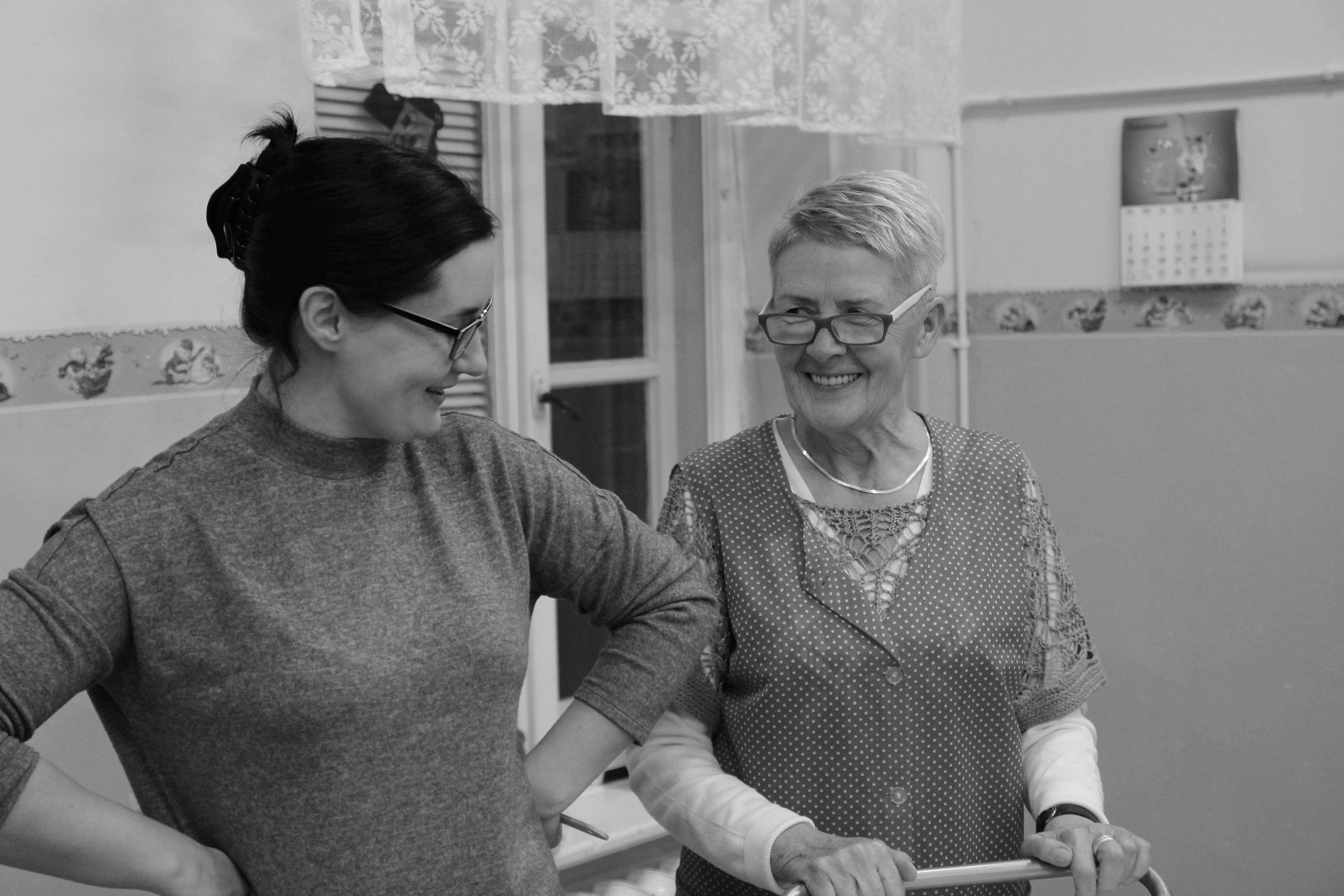 zdjęcie z projektu Dzwięczące wieżowce. Dwie aktorki w okularach usmiechaja się do siebie.