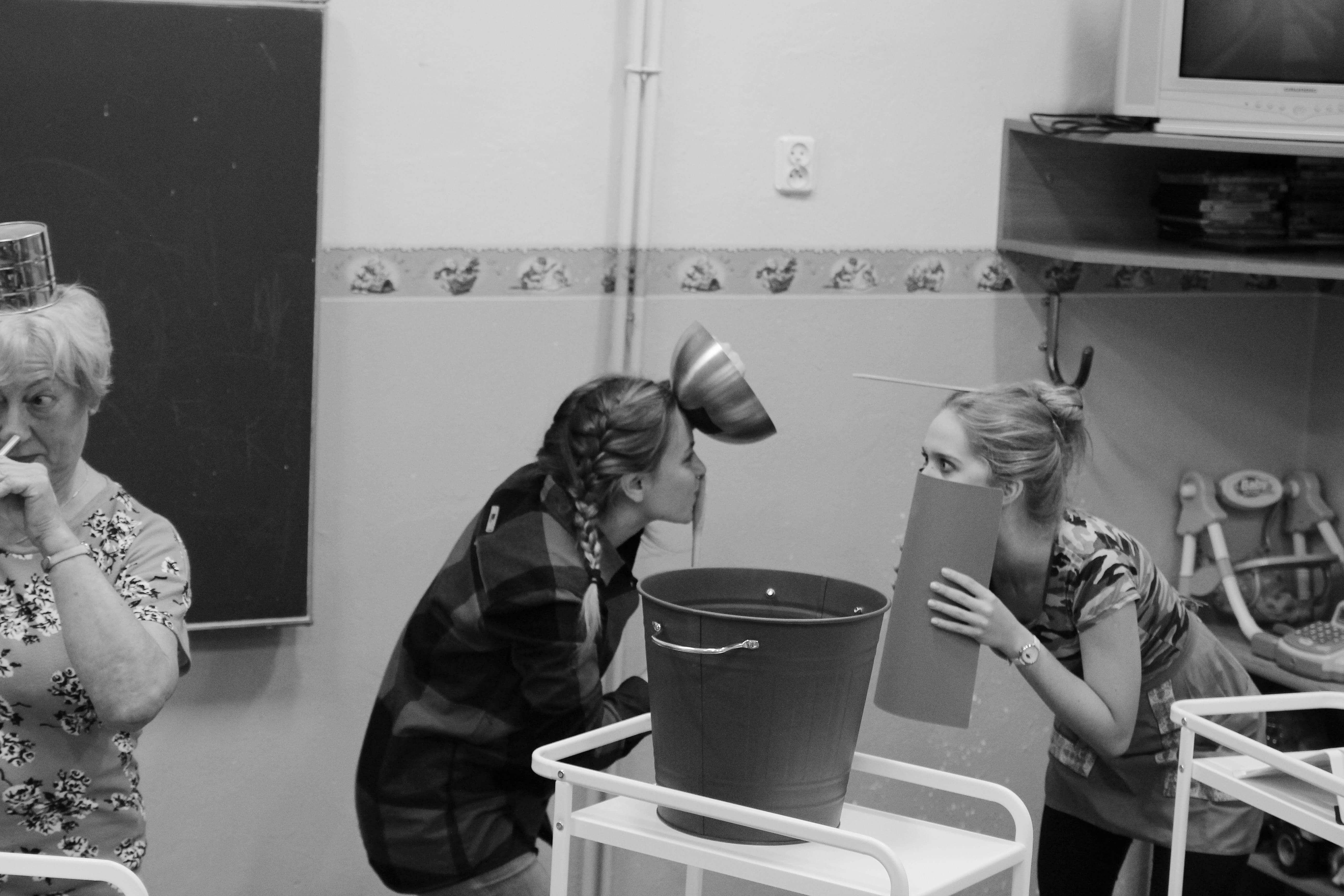 zdjęcie z projektu Dzwięczące wieżowce. Dwie aktorki wygłupiają się na scenie. Jedna przykłada miskę do czoła, druga zakrywa usta kartka papieru, trzecia ma na głowie kubek i słomkę w nosie.