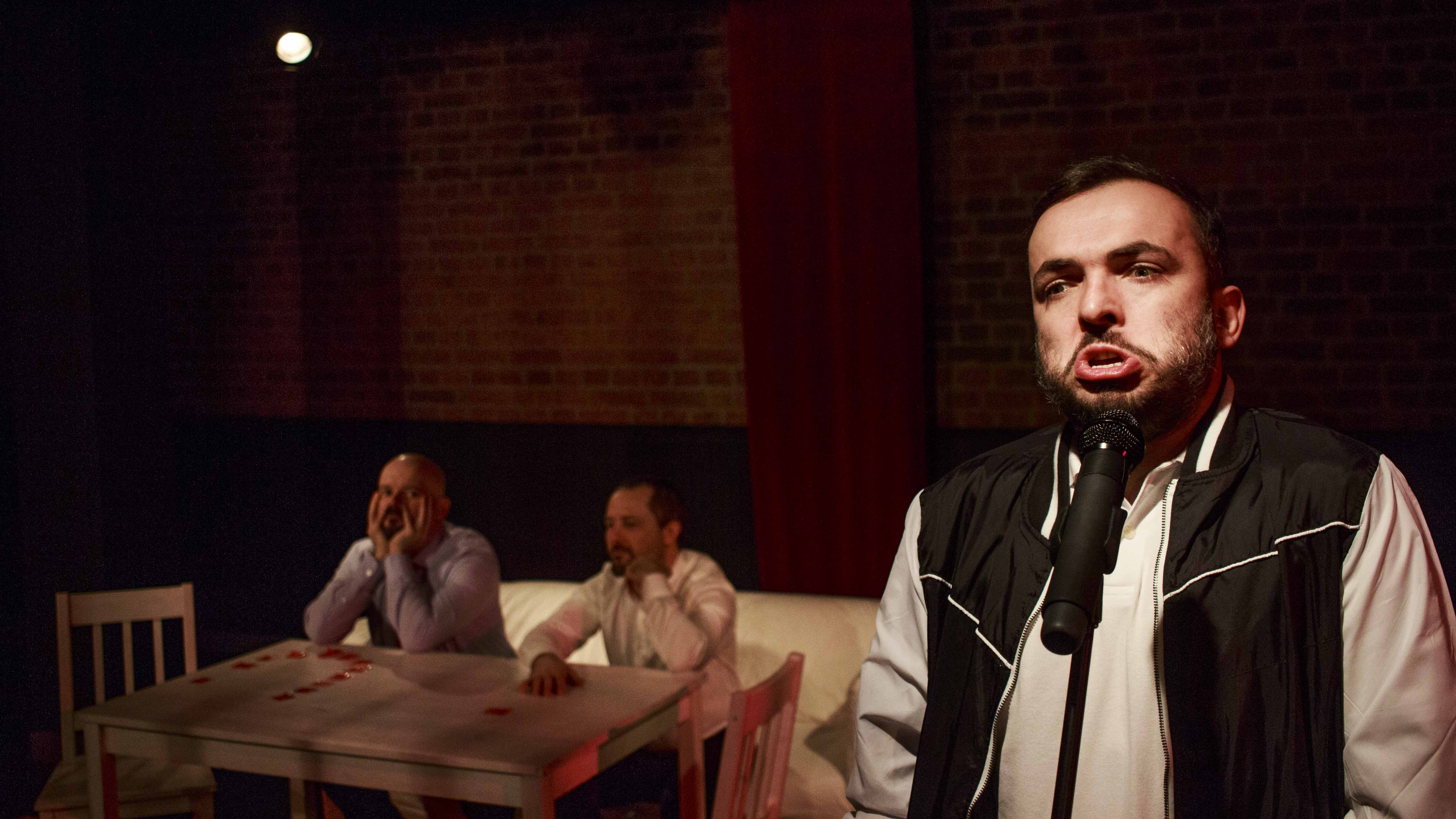 Zdjęcie do spektaklu Dobroć nasza dobroć. Aktor stoi przy mikrofonie. W tle dwóch pozotałych aktorów siedzi przy stole.