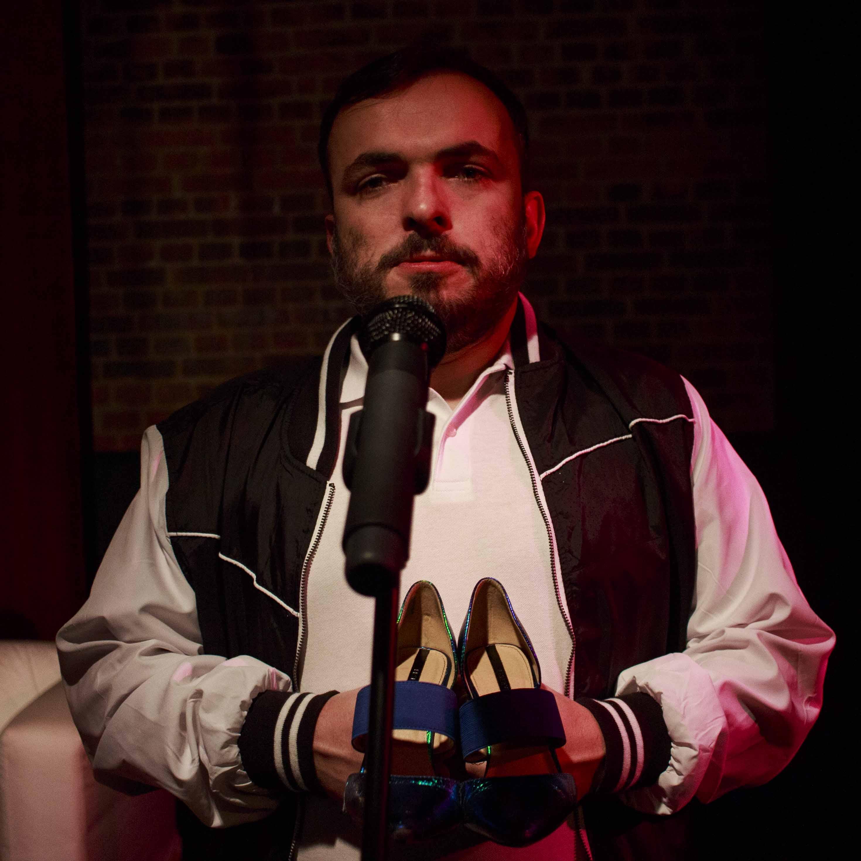 Zdjęcie do spektaklu Dobroć nasza dobroć. Aktor stoi przy mikrofonie. Trzyma w rękach damskie buty.