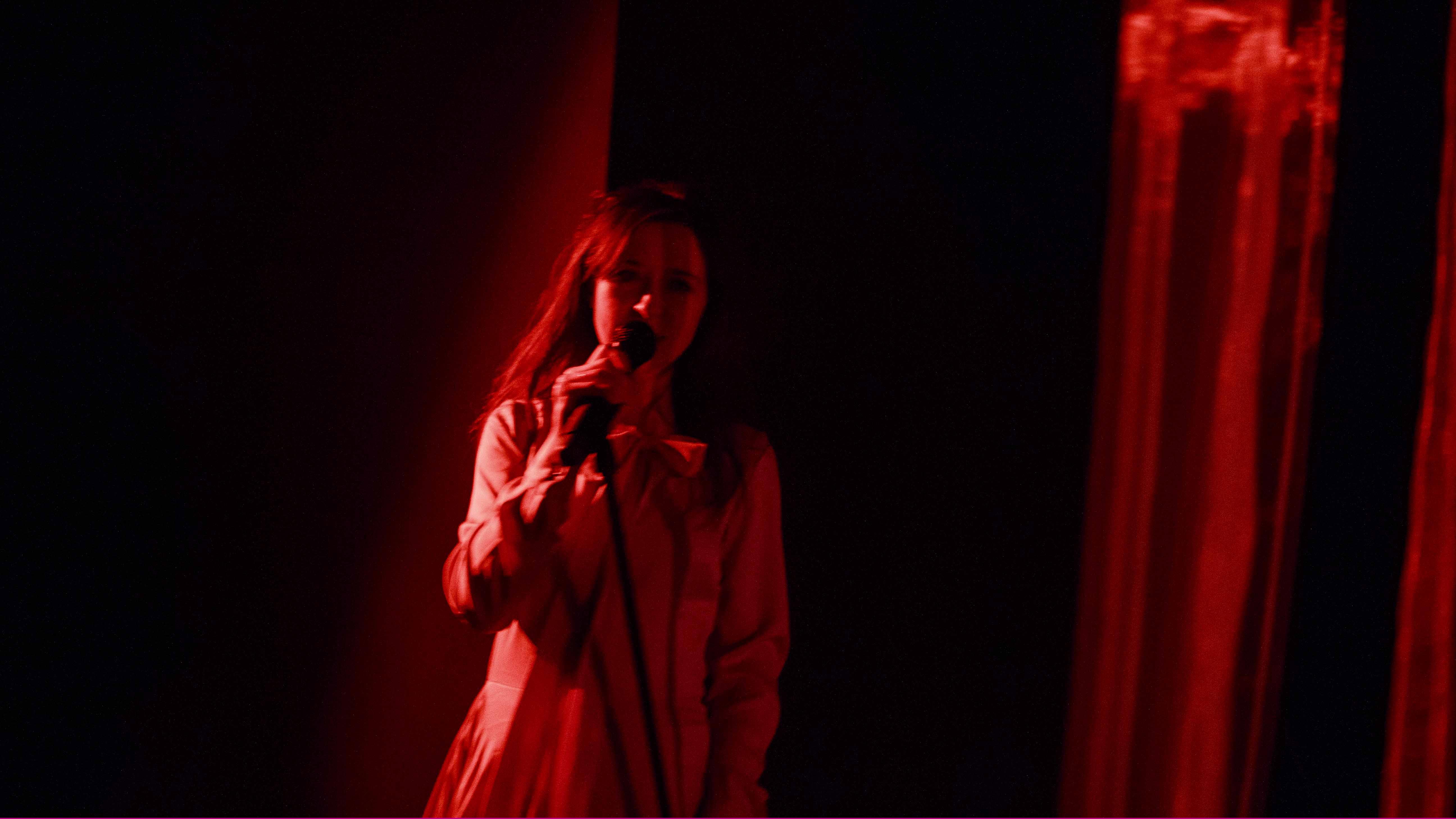 Zdjęcie do spektaklu Dobroć nasza dobroć. Aktorka w czerwonym świetle śpiewa do mikrofonu.