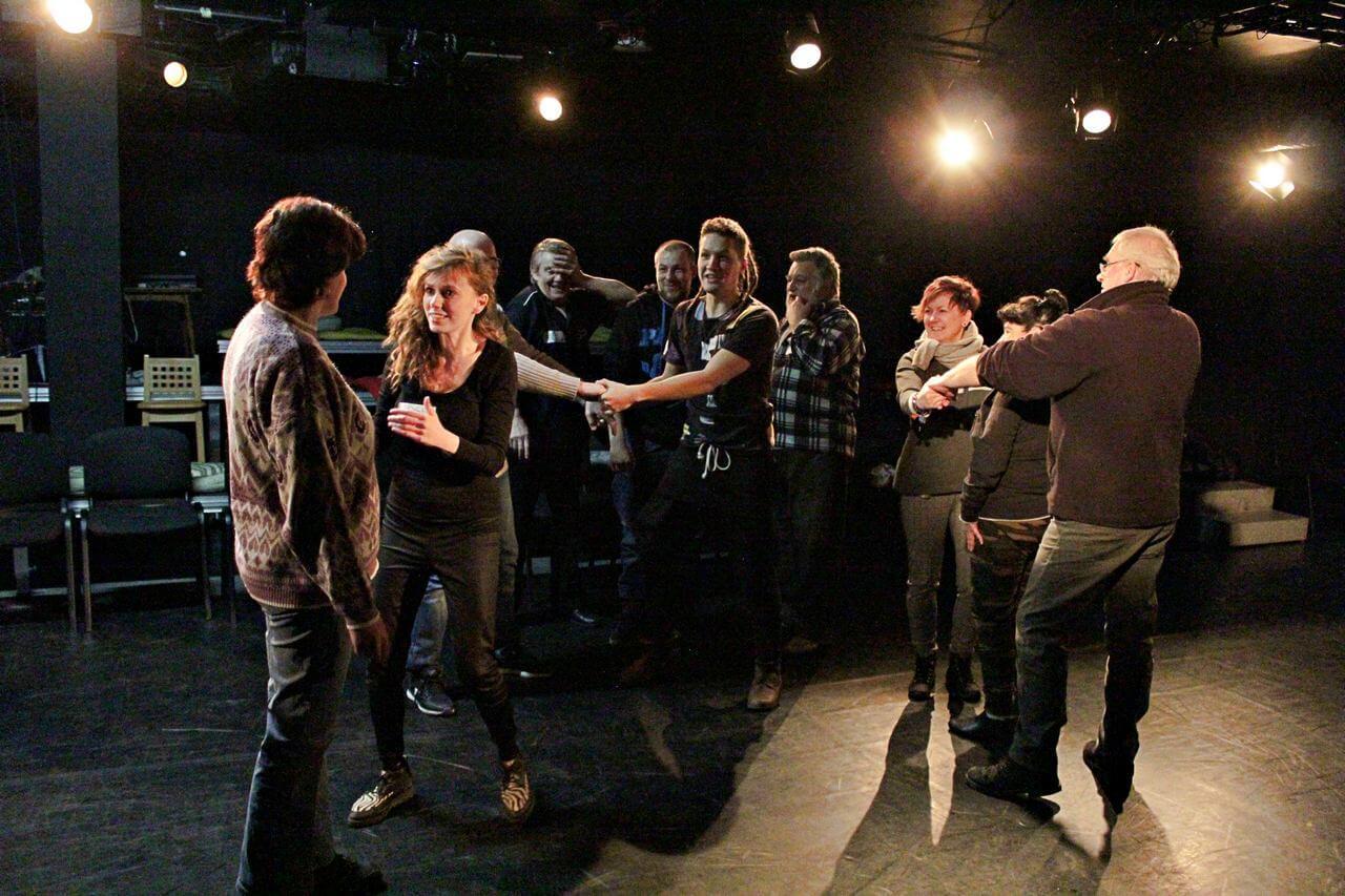 Zdjęcie z projektu Kulturalny Utrecht. Na zdjęciu grupa uczestników w róznym wieku podczas ćwiczeń. Trzymają się za ręce.