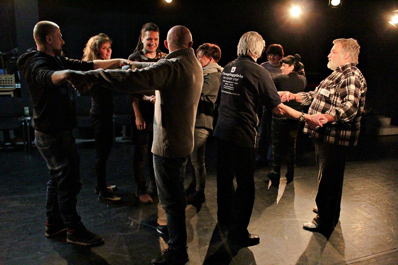 Zdjęcie z projektu Kulturalny Utrecht. Na zdjęciu grupa uczestników w róznym wieku podczas ćwiczeń. Tworzą kółka, trzymają się za ręce.