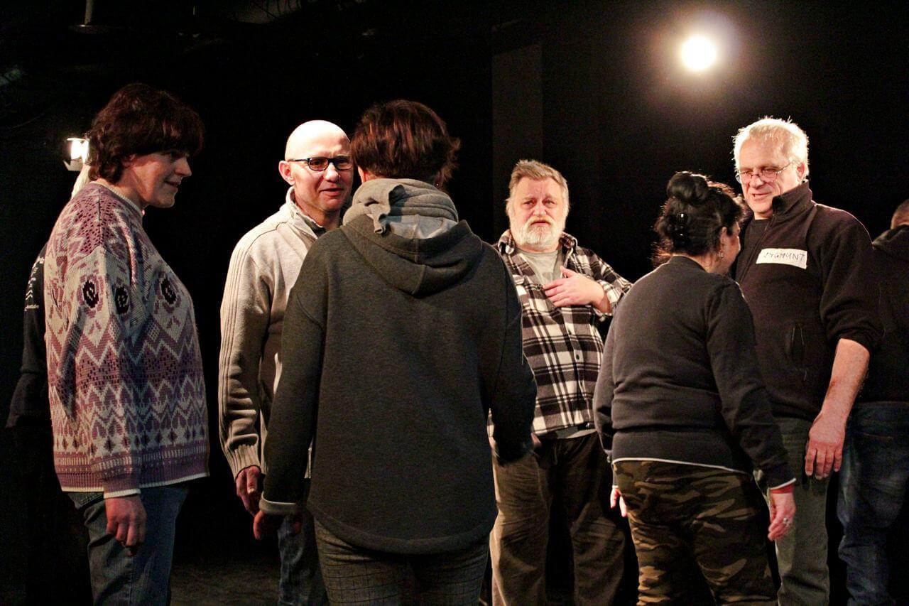 Zdjęcie z projektu Kulturalny Utrecht. Na zdjęciu grupa uczestników w róznym wieku podczas ćwiczeń. Stoja na wprost siebie.