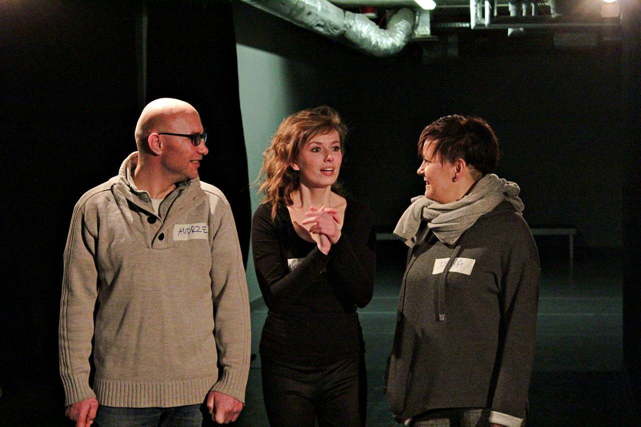 Zdjęcie z projektu Kulturalny Utrecht. Trójka uczestników. Po lewo mężczyzna, po prawo kobieta. Kobieta po srodku trzyma splecionie dłonie na wysokości szyi.