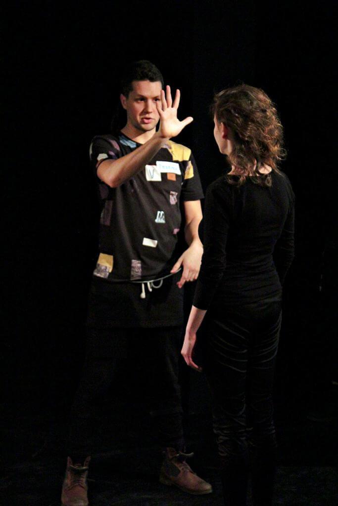 Zdjęcie z projektu Kulturalny Utrecht. Aktor podnosi szeroko otwarta dłoń na wysokość twarzy aktorki. Aktor sto przodem, aktorka tyłem.