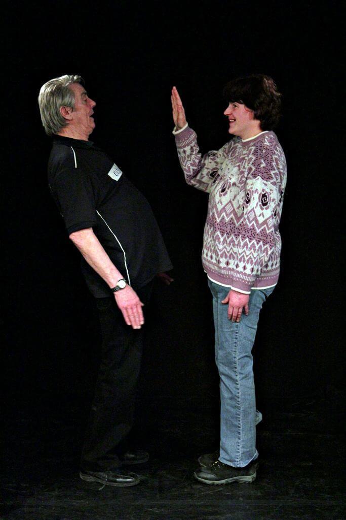 Zdjęcie z projektu Kulturalny Utrecht. Kobieta w wzorzystym swetrze, stoi na przeciwko mężczyzny w czarnym ubraniu. Podnosi dłoń na wysokośc jego twarzy.