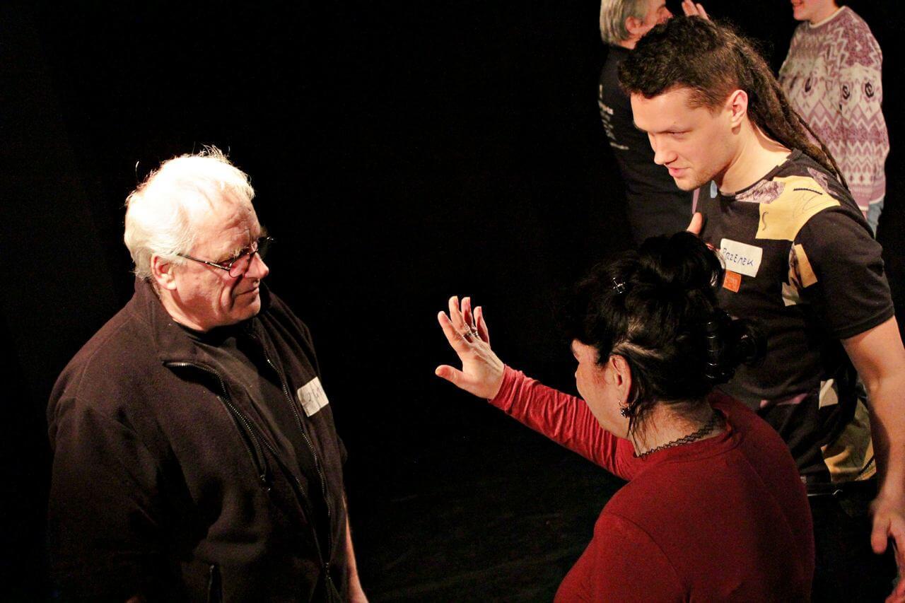 Zdjęcie z projektu Kulturalny Utrecht. Kobieta w czerwonej bluzce, podnosi dłoń na wysokość twarzy siwego mężczyzny w okularach.
