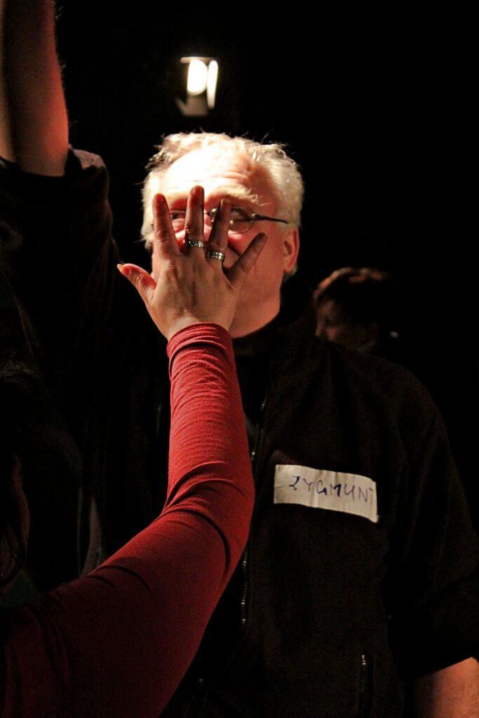 Zdjęcie z projektu Kulturalny Utrecht. Twarz mężczyzny zakryta przez wyciągniętą dłoń kobiety w czerwonej bluzce.