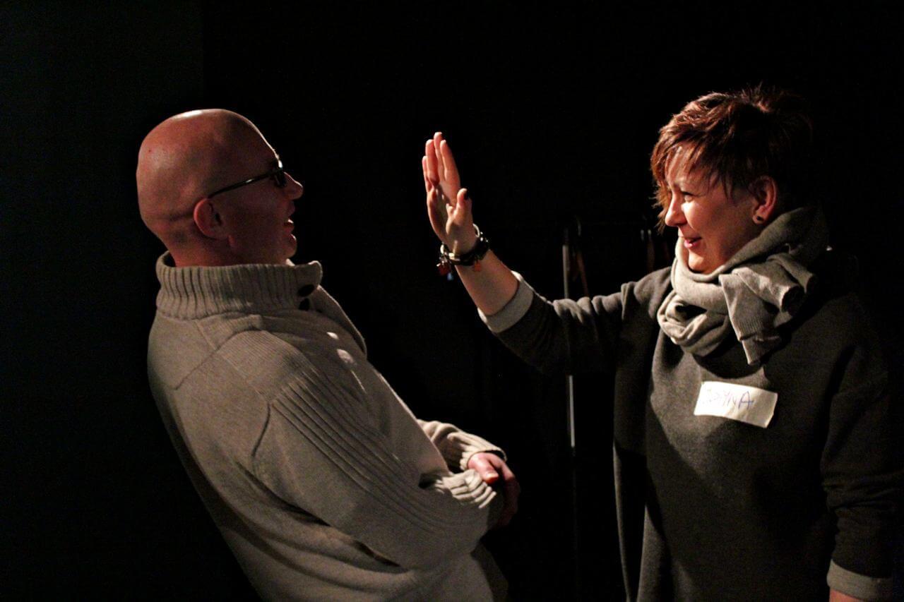 Zdjęcie z projektu Kulturalny Utrecht. Kobieta unosi dłoń na wysokośc twarzy mężczyzny. Mężczyzna odchyla się do tyłu.