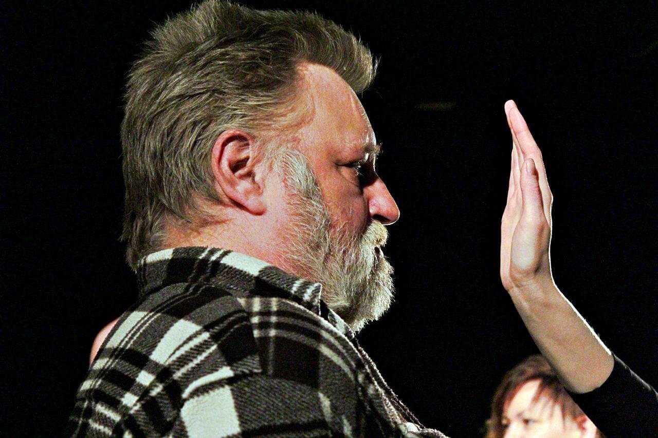 Zdjęcie z projektu Kulturalny Utrecht. Mężczyzna w koszuli w krate. Kobieta unosi dłoń na wysokośc twarzy mężczyzny. Widac tylko jej dłoń.