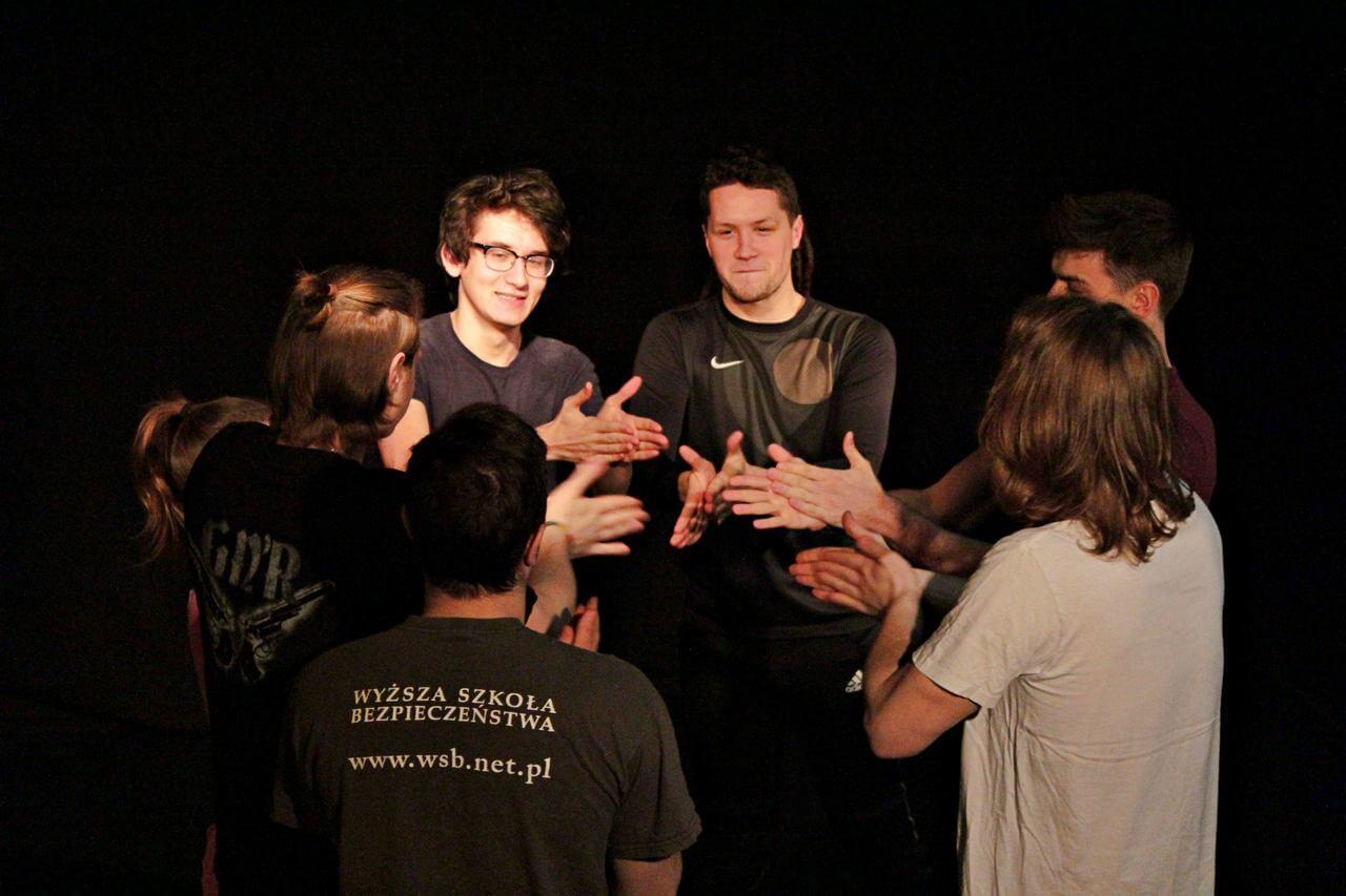 Zdjęcie z projektu Teatr Młodych. Grupa uczestników w kole. Ręce wyciagaja w kierunku wnętzra koła.
