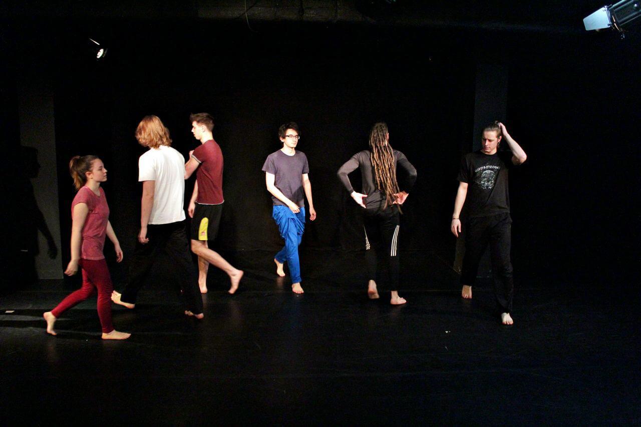 Zdjęcie z projektu Teatr Młodych. Uczestnicy chodza po czarnej podłodze.