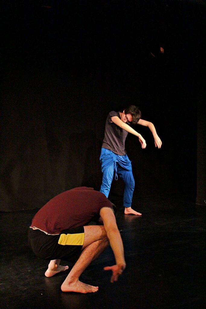 Zdjęcie z projektu Teatr Młodych. Uczestnicy ćwiczą na czarnej sali teatralnej.