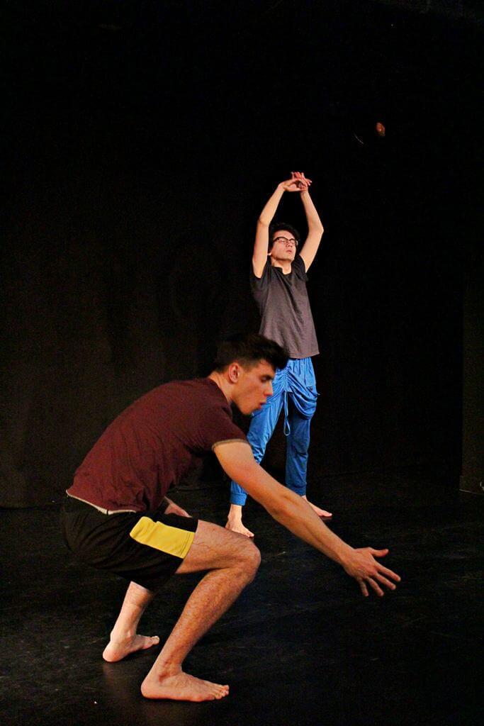 Zdjęcie z projektu Teatr Młodych. Uczestnicy ćwiczą na czarnej sali teatralnej. Jeden kuca, drugi podnosi ręce do góry.
