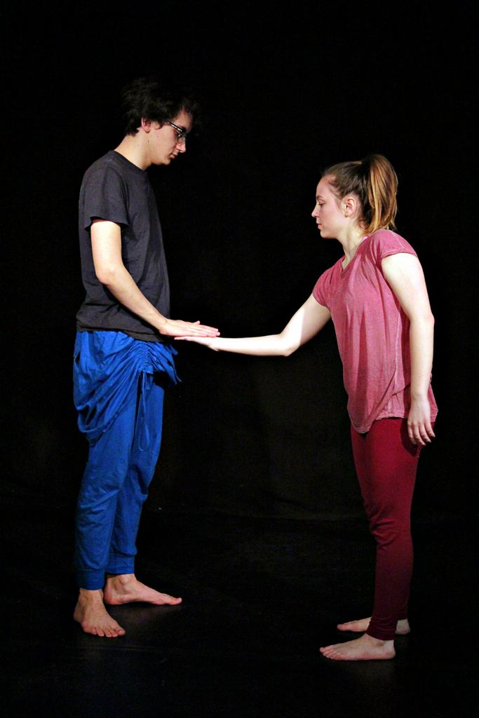 Zdjęcie z projektu Teatr Młodych. Uczestnicy ćwiczą na czarnej sali teatralnej. Chłpak w niebieskich spodniach podaję rękę dziewczynie ubranej na czerwono.