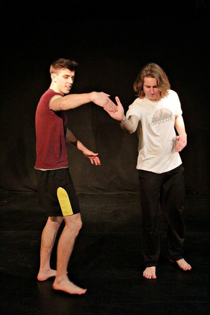 Zdjęcie z projektu Teatr Młodych. Uczestnicy ćwiczą na czarnej sali teatralnej. Dwóch chłopaków styka się dłoniami. jedem ma krótkie spodenki i czerwoną koszulkę, drugi czarne spodnie i białą koszulkę.