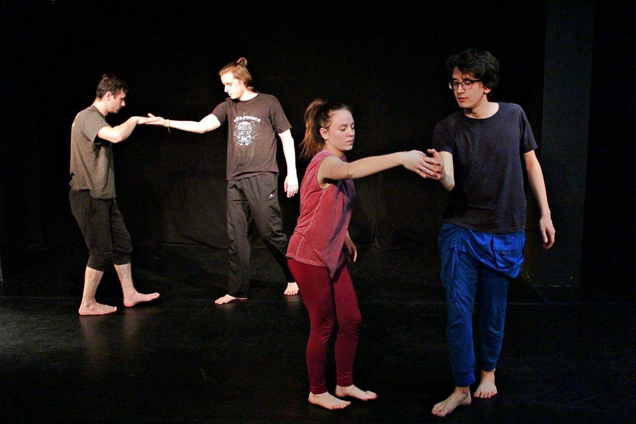 Zdjęcie z projektu Teatr Młodych. Uczestnicy ćwiczą na czarnej sali teatralnej. Stykają się dłońmi.