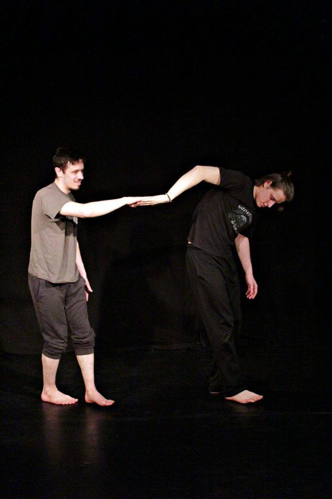Zdjęcie z projektu Teatr Młodych. Uczestnicy ćwiczą na czarnej sali teatralnej. Dwóch chłopaków jeden za drugim, stykają się dłońmi.
