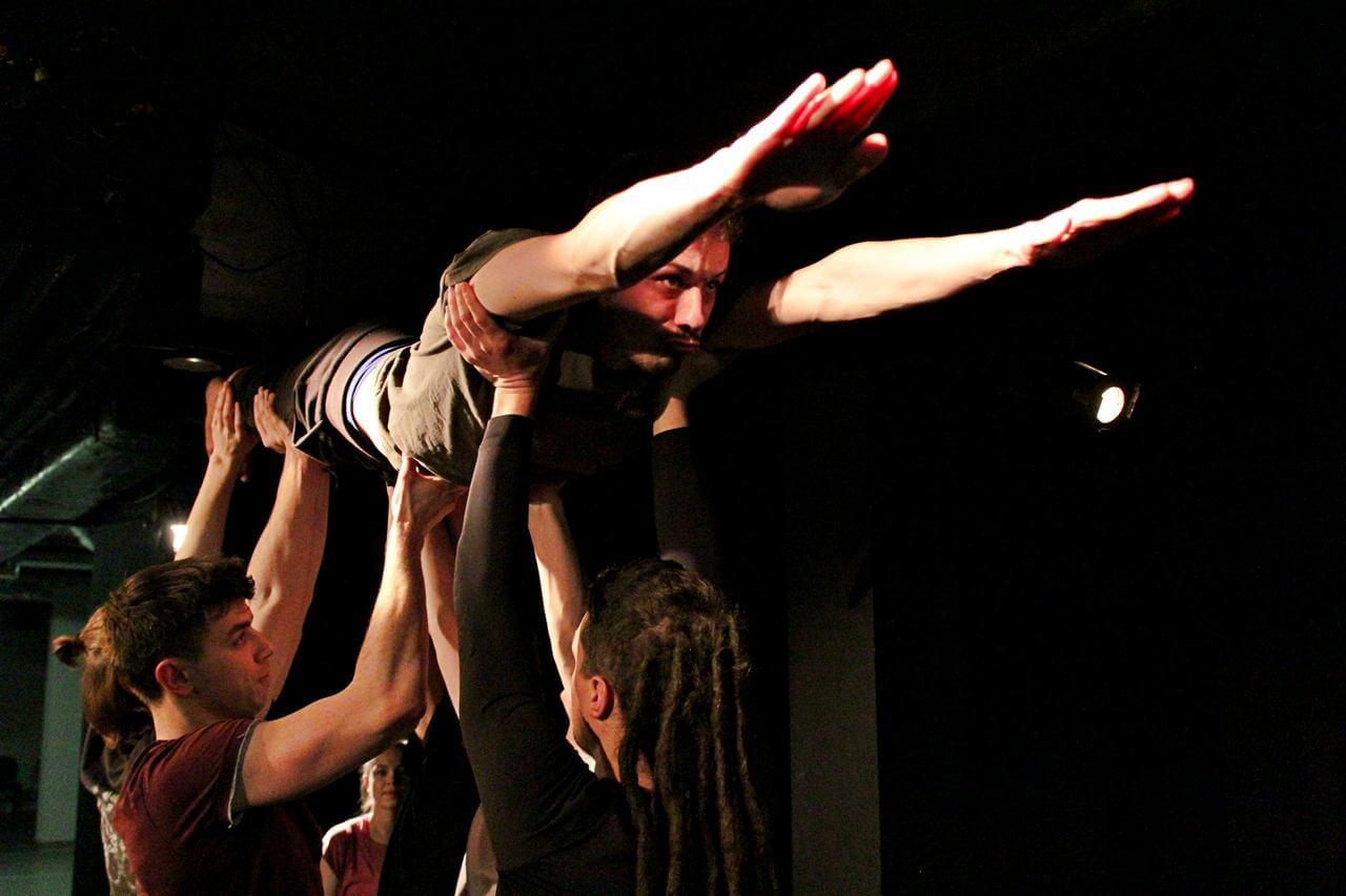 Zdjęcie z projektu Teatr Młodych. Uczestnicy ćwiczą na czarnej sali teatralnej. Kilku uczestnikó unusi jednego z nich w pozycji leżącej do góry.