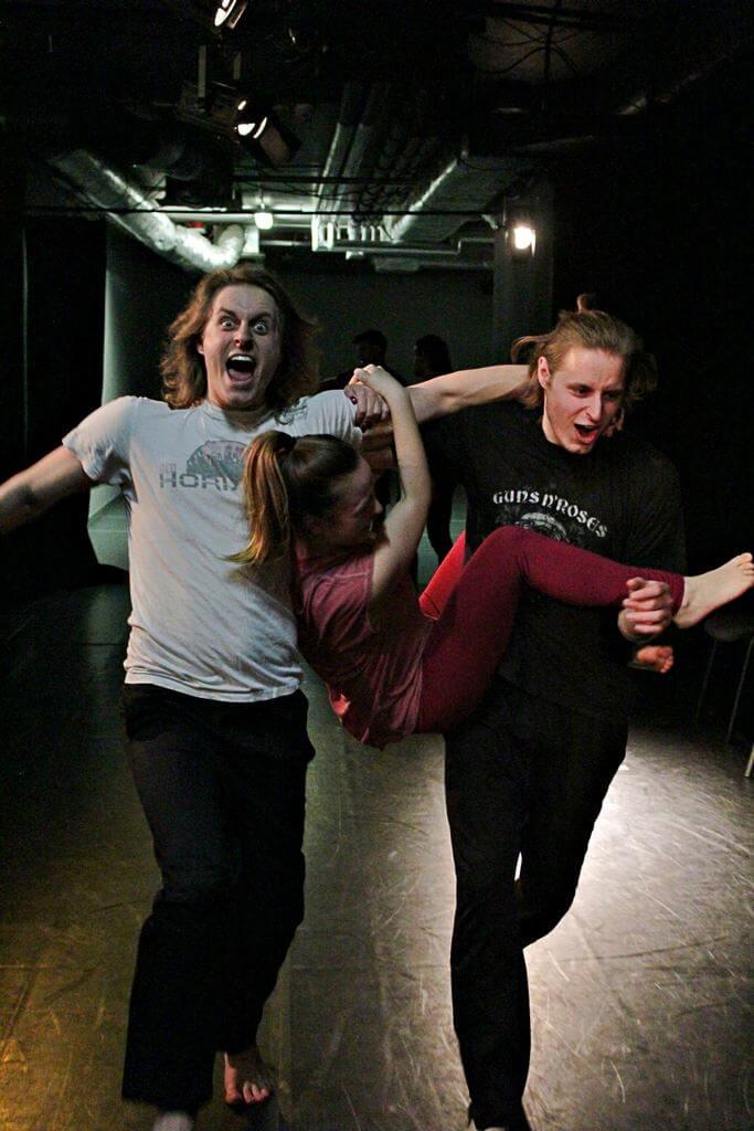 Zdjęcie z projektu Teatr Młodych. Uczestnicy ćwiczą na czarnej sali teatralnej. Dwóch chłopaków niesie dziewczynę zawieszoną pomiędzy nimi.