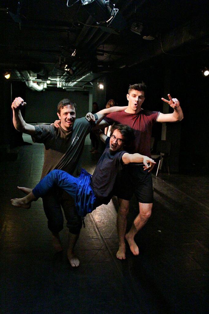 Zdjęcie z projektu Teatr Młodych. Uczestnicy ćwiczą na czarnej sali teatralnej. Dwóch chłopaków niesie trzeciego, zawieszonego na rękach pomiędzy nimi.