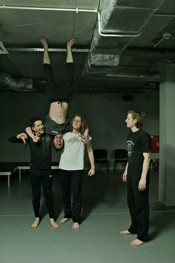 Zdjęcie z projektu Teatr Młodych. Uczestnicy ćwiczą na sali teatralnej. Dóch chłopaków trzyma na ramionach trzeciego, odwróconego do góry nogami. Stopy trzyma oparte o sufit.