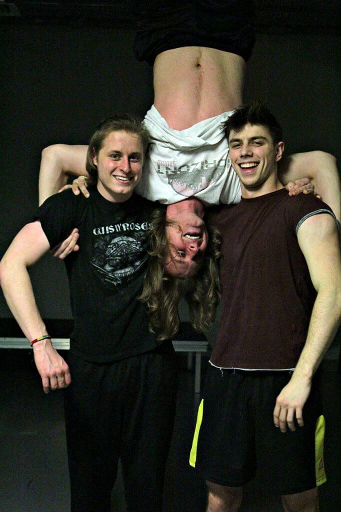 Zdjęcie z projektu Teatr Młodych. Uczestnicy ćwiczą na sali teatralnej. Dwóch chłopaków trzyma na ramionach trzeciego odwróconego do góry nogami.