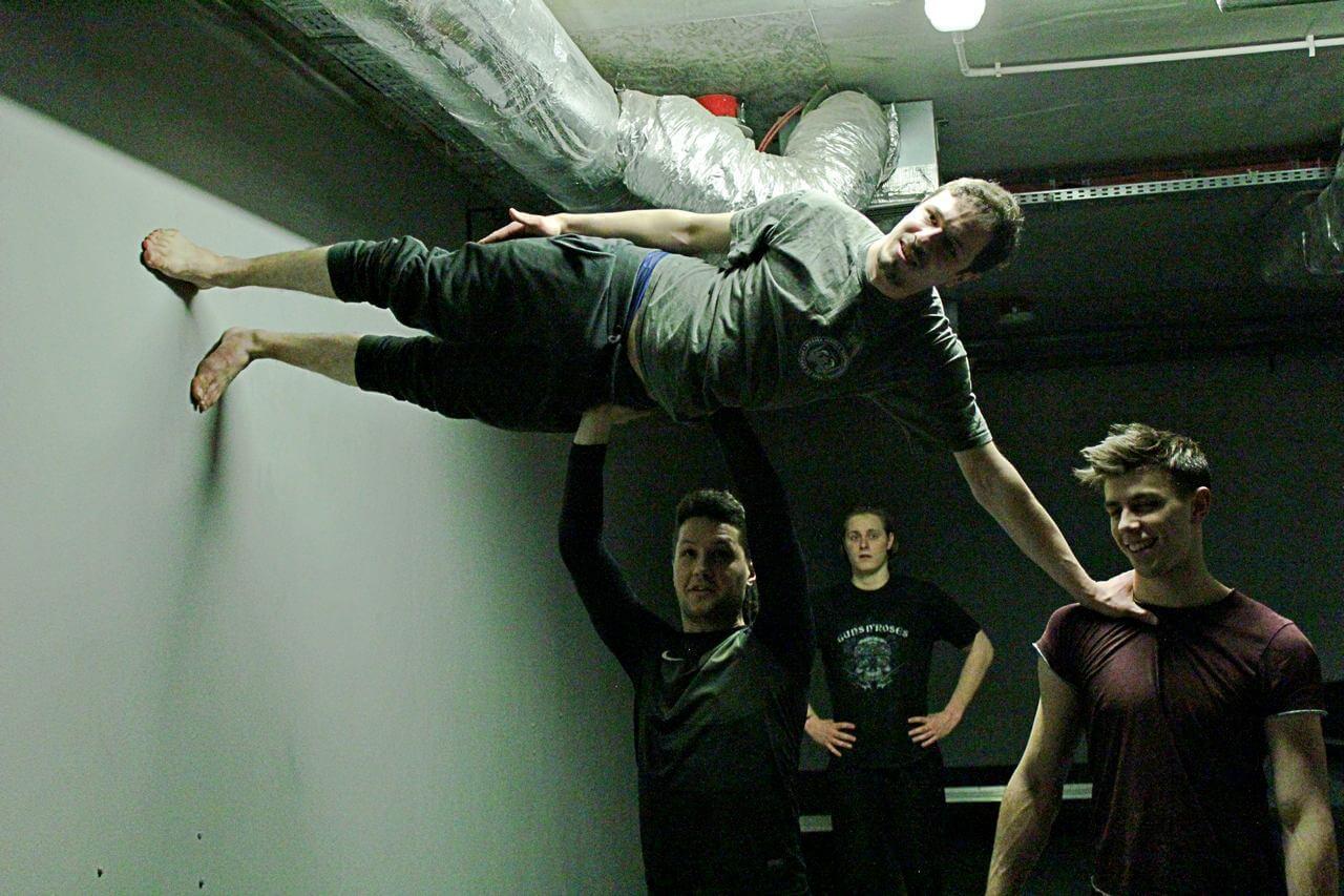 Zdjęcie z projektu Teatr Młodych. Uczestnicy ćwiczą na sali teatralnej. Dwóch chłopaków unosi trzeciego bokiem do góry, jego stopy sa opartę o ścianę.