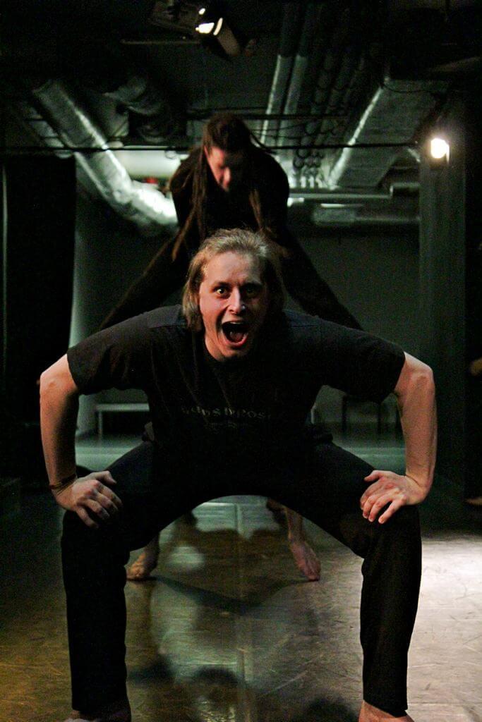 Zdjęcie z projektu Teatr Młodych. Uczestnicy ćwiczą na sali teatralnej. Uczestnicy ustawieni w rzędzie, w przysiadzie. jeden przeskakuje nad nimi.